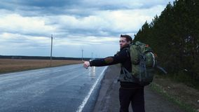 The traveler is trying to stop the car in cloudy weather. A tourist hitchhiker walks along the road with a backpack on his shoulders, lifting his thumb up stock video