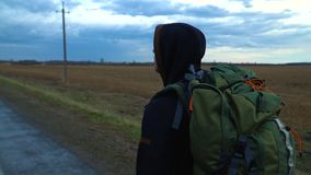 A young tourist travels with a backpack on his shoulders. A tourist hitchhiker walks along the road with a backpack on his shoulders. The weather is cloudy and stock video