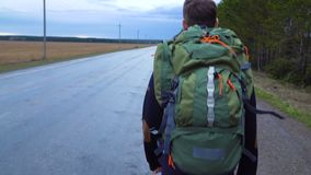A young tourist travels with a backpack on his shoulders. A tourist hitchhiker walks along the road with a backpack on his shoulders. The weather is cloudy and stock footage