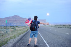 Tourist hitchhiking along a desolate road Royalty Free Stock Photo