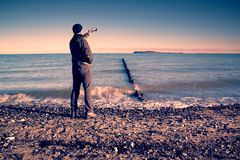 Tourist hold cellphone, take picture of autumn  sea scenery at breakwater.  Vivid and vignetting effect. Royalty Free Stock Images