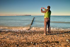 Tourist hold cellphone, take picture of autumn  sea scenery at breakwater.  Vivid and vignetting effect. Royalty Free Stock Photography