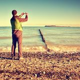 Tourist hold cellphone, take picture of autumn  sea scenery at breakwater.  Vivid and vignetting effect. Royalty Free Stock Photos