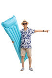 Tourist holding an air mattress and pointing right. Full length portrait of a tourist holding an air mattress and pointing right isolated on white background Stock Photography