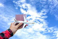 Tourist holding airplane flight travel and passport traveller fly travelling citizenship air on blue sky background. Travel Concept Stock Images