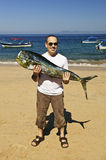 Tourist holding big fish on beach Stock Photography