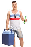 Tourist holding a cooling box and a bottle of beer Stock Photo