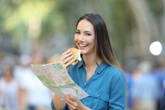 Tourist holding a map and a burger in the street. Happy tourist holding a paper map and a burger in the street royalty free stock image
