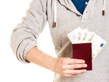 Tourist holding passport full of money. Stock Images