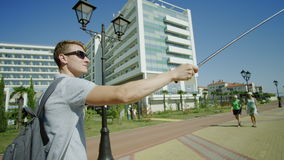 Tourist holding selfie stick and taking photos. Traveller holding selfie stick. man walking and taking photo stock footage