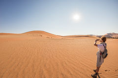 Tourist holding smart phone and taking photo at scenic sand dunes at Sossusvlei, Namib desert, Namib Naukluft National Park, Namib. Ia. Adventure and exploration Royalty Free Stock Images