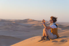 Tourist holding smart phone and taking photo at scenic sand dunes at Sossusvlei, Namib desert, Namib Naukluft National Park, Namib. Ia. Adventure and exploration Stock Photography