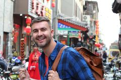 Tourist holding sugar-coated haws on a stick in China.  royalty free stock images