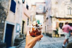 Tourist holds Fritule on street in Croatia. Croatian homemade fr. Tourist holds in hand Fritule little doughnuts balls with chocolate on background of streets of stock photography