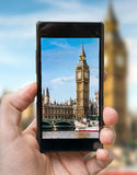 Tourist holds smartphone in hand and photographing Big Ben in London Stock Photography