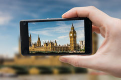 Tourist holds smartphone in hand and photographing Big Ben in London Royalty Free Stock Photos