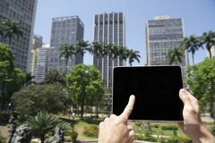 Tourist Holds Touchscreen Tablet Sao Paulo Brazil City Center. Tourist businessman holds touchscreen tablet computer with blank screen in a plaza in the downtown Royalty Free Stock Image