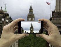 Tourist holds up camera mobile at big ben in flag Stock Photo