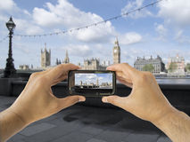 Tourist holds up camera mobile at big ben Stock Photography