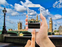 Tourist holds up camera mobile at big ben Royalty Free Stock Images