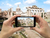 Tourist holds up camera mobile at forum in Rome Stock Image