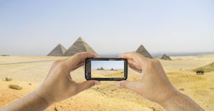 Tourist holds up camera mobile at  pyramids Stock Images