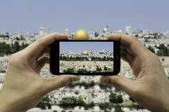 Tourist holds up camera phone at the jerusalem. Tourist takes a picture with his mobile of the Jerusalem old city Royalty Free Stock Images