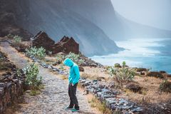 Tourist in hoodie in Aranhas valley hiking from Cruzina to Ponta do Sol. Huge mountains of coastline and old local stone royalty free stock photo