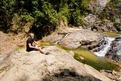 Tourist on Huai Sakae waterfall. Male tourist in Huai Sakae waterfall in Khao Phanom Bencha Krabi southern Thailand. Landscape in real rainforest taken in Stock Photo