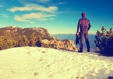 Tourist im Schwarzen steht auf felsigem Standpunkt und passt in nebelhafte felsige Berge auf Fogywintermorgen in den Alpen Lizenzfreies Stockbild
