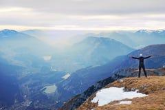 Tourist im Schwarzen steht auf felsigem Standpunkt und passt in nebelhafte felsige Berge auf Fogywintermorgen in den Alpen Stockfotos