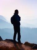 Tourist im Windcheater mit sportlichem Rucksack und Pfosten in den Händen stehen auf felsigem Standpunkt und dem Aufpassen in tie Lizenzfreies Stockbild