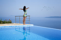 Tourist on infinity pool with outstretched arms. And flock of birds Royalty Free Stock Photography