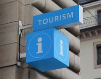 Tourist information sign. The close up view of blue tourist information sign with building in the background Royalty Free Stock Image
