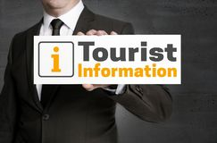 Tourist information signboard is held by businessman.  Stock Photos