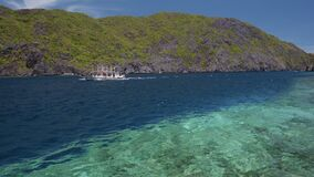 Tourist island hopping boat in ocean strait with rippled surface. Matinloc island. Tour C. Bacuit Archipelago