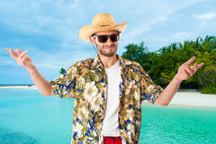 Tourist on the island. A young, attractive male in a colorful outfit in a tropical island setting as a stereotype tourist stock image