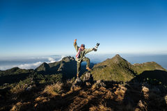 Tourist jump on mountain peak view cloud layer background Royalty Free Stock Photography