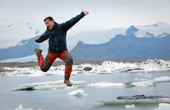 Tourist jumpinf in front of glacier lake, Iceland Stock Photo