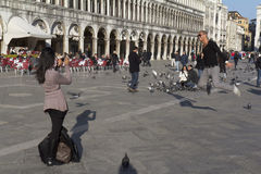 Tourist jumping up at St Mark Square Royalty Free Stock Photography