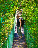 Tourist on a jungle bridge stock photos
