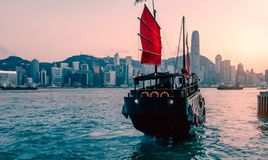 Tourist junk boat in Hong Kong. Tourist junk boat in Hong Kong moving from Kowloon harbour at Victoria harbour in the evening royalty free stock image