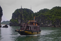 Tourist junk navigates through the karst islands Royalty Free Stock Photo