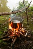 Tourist kettle. Above a fire on coast Stock Photography