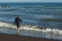 Tourist on the Khalaktyrsky beach with black sand. Pacific Ocean washes Kamchatka Peninsula. Stock Photo