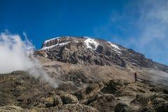 Tourist and Kibo peak in Mount Kilimanjaro, Tanzania royalty free stock photography