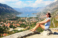 Tourist in Kotor. Young woman relaxing in the sun overlooking the Kotor bay with a cruise ship at anchor in the distance Stock Photo