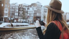 Tourist lady takes photos of old architecture. Girl with long hair and red backpack enjoying amazing city scenery. 4K. Tourist lady takes photos of old stock video footage