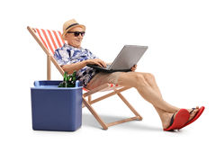 Tourist with laptop in deck chair next to cooling box Royalty Free Stock Photos