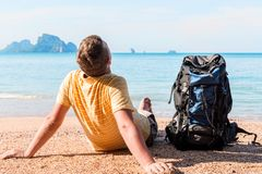 Tourist with a large backpack relaxes on the beach near the sea. With a beautiful view of the mountains Royalty Free Stock Images